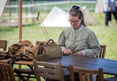 Eine Frau flickt Hosen an einem Tisch im Lager. (Bild: Reto Martin)