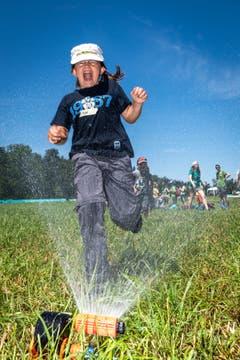 Ein erfrischender Sprung durch den Rasensprenger. (Bild: Christian H. Hildebrand, Hagendorn, 8. Juni 2019)