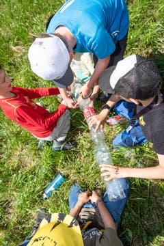 Diese Kinder bauen eine Wasserpipeline aus Petflaschen. (Bild: Christian H. Hildebrand, Hagendorn, 8. Juni 2019)