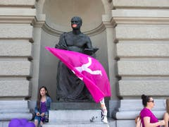 Männliche Statue mit roten Lippen und Fahne am Bundeshaus streikt mit. (Bild: KEYSTONE/PETER KLAUNZER)