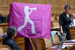 Margret Kiener Nellen, SP Kanton BE, verdeckt, zeigt neben Flavia Wasserfallen, SP Kanton BE (rechts), eine Flagge des Frauenstreiks im Nationalrat. (Bild: KEYSTONE/Peter Klaunzer)