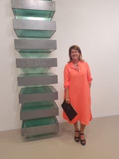 Siska Dezutter, Kunstsammlerin aus Brüssel, posiert im orangefarbenen Hemdkleid vor einer Wandinstallation von Donald Judd.