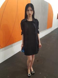 Jian Xu, die Mitarbeiterin eines Auktionshauses in Hongkong ist nach Basel gekommen, um ihre Privatsammlung zu erweitern. Sie trägt ein schwarzes Kleid der Designerin Ann Demeulemeester.