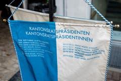 Eine Flagge mit den Namen der letzten Kantonsratspräsidentinnen und Kantonsratspräsidenten steht neben dem Rednerpult.