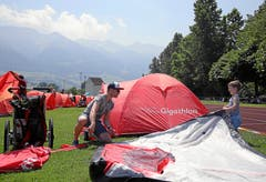 Trotz grosser Hitze bauen viele Gigathleten ihr Zelt bereits am Mittag auf. Bis zum Abend entsteht hier in Sarnen das rote Gigathlon-Camp.