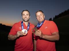 Schöner Abschluss einer langen Wartezeit: Bei Einbruch der Nacht zeigen Alex Baumann (li.) und Beat Hefti nochmals ihre Goldmedaillen (Bild: KEYSTONE/URS FLUEELER)