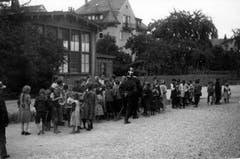 August 1914: Der Erste Weltkrieg ist erst ein paar Monate alt. Beim Restaurant Hirschen in St.Fiden stehen Frauen und Kinder für Suppe an, die von Soldaten verteilt wird. In der Bildmitte ist mit dem Rücken zur Kamera ein Kavallerist abgebildet. Zu erkennen ist er am Tschako mit weissem Pinsel und dem Säbel.