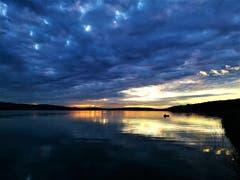 Mystische Abendstimmung beim Sonnenuntergang am Sempachersee mit einem Fischer im Boot. (Bild: Urs Gutfleisch, Sempach, 11. Juli 2019)