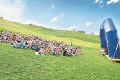 Die Teilnehmer des Rontallagers machen es sich auf der Wiese vor der Bühne bequem. (Bild: Ralph Ribi, Gontenbad, 17. Juli 2019)