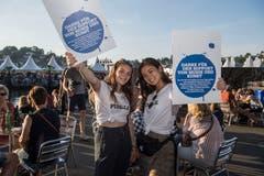 Paulina Appel (links) und Sae Fontana versuchen, die blauen Pins an die Besucher zu bringen. (Bild: Nadia Schärli, Luzern, 19. Juli 2019)