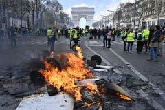 Protestierende Gilets jaunes vor brennenden Barrikaden auf den Champs-Élysées. (Bild: Getty Images)