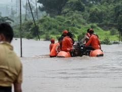 Die Bahnreisenden wurden in Rettungswesten mit Schlauchbooten durch das trübe braune Wasser abtransportiert. (Bild: KEYSTONE/EPA/DIVYAKANT SOLANKI)