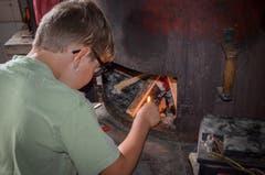 Martin jun. entfacht das Feuer unter dem Käsekessi.