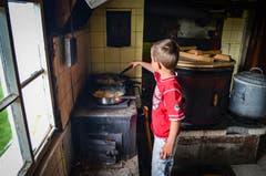 Samuel wendet die Rösti, die in zwei Pfannen auf dem Holzkochherd gebraten wird.
