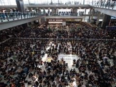 Tausende Demonstranten versammelten sich in der Abflug- und Ankunftshalle des internationalen Flughafens in Hongkong, um gegen die Regierung und die Polizeigewalt zu protestieren. (Bild: KEYSTONE/AP/VINCENT THIAN)