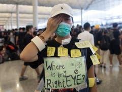 Aktivisten skandierten im Flughafen Parolen: Die Polizei solle einem Demonstranten, der durch ein Gummigeschoss schwer im Gesicht verletzt worden war, sein Auge «zurückgeben». (Bild: KEYSTONE/EPA/JEROME FAVRE)