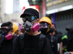 Demonstrierende tragen bei den Protesten in Hongkong Schutzmasken. (Bild: KEYSTONE/EPA/JEROME FAVRE)