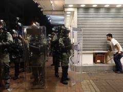 Ein Mann schliesst in Hongkong sein Geschäft, weil er Ausschreitungen und Sachbeschädigungen befürchtet. (Bild: KEYSTONE/EPA/JEROME FAVRE)