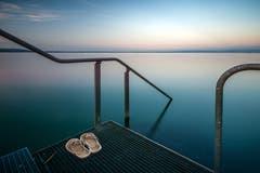 In der Abenddämmerung hat das Schwimmen im See einen besondern Reiz, aufgenommen an der Badeplattform des Schiffstegs in Altnau. (Bild: Wolfgang Reisser)