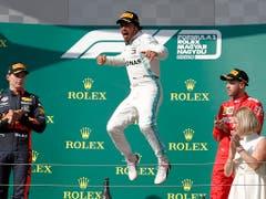 Ein Sieg wie eine Erlösung: Lewis Hamiltons Luftsprung bei der Siegerehrung, flankiert von Max Verstappen (links) und Sebastian Vettel (rechts). (Bild: KEYSTONE/AP/LASZLO BALOGH)