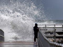 Ein Fischer in Florida trotzt den Riesenwellen. (Bild: KEYSTONE/AP Orlando Sentinel/JOE BURBANK)