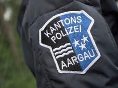 Das Logo der Kantonspolizei Aargau auf der Uniform eines Polizisten: Laut Polizei war ein 39-Jähriger betrunken in seinem neuen Tesla unterwegs, auf dem Schoss sein Kind. (Bild: KEYSTONE/URS FLUEELER)