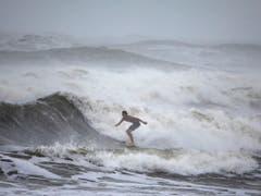 Der Hurrikan zog am Mittwoch weiter nach Norden, entlang der Südostküste der USA - allerdings deutlich abgeschwächt, als Hurrikan der Kategorie zwei. Anders als ursprünglich befürchtet, traf «Dorian» die US-Küste aber nicht direkt. - Ein Mann beim Surfen am Mittwoch in Ormond Beach, Florida. (Bild: KEYSTONE/EPA/JIM LO SCALZO)