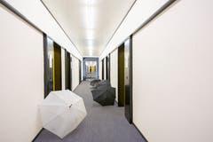 Kunst am Bau, die dem herrschenden Regenwetter geschuldet ist: In einem Korridor drapierte Regenschirme. (Bild: Urs Bucher - 21. August 2019)