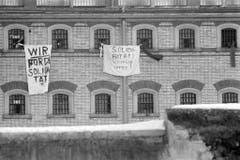 Während der Kundgebung für Walter Stürm vor dem Tor der Strafanstalt Regensdorf am 13. Dezember 1980 in Zürich zeigen Insassen ihrerseits mit vor den Fenstern beschrifteten Leintüchern ihre Solidarität mit den Demonstranten. (Bild: Keystone)