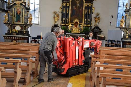 Der aufklappbare Kran wird durch die engen Kirchenbänke geschoben.