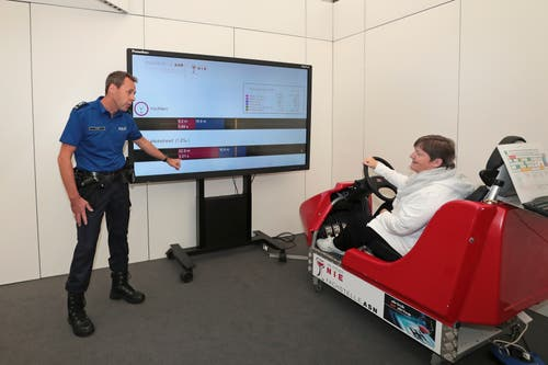 Brigitte Meier aus Wädenswil testet ihre Fahrfähigkeit unter simuliertem Alkoholeinfluss, beobachtet von Polizist Harald Hirzel. (Bild: Roger Zbinden (Zug, 20. Oktober 2018))