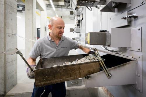 Paul Gisler nimmt drei Stunden nach dem Start des Kremationsprozesses die Überreste aus dem Ofen. (Bild: Philipp Schmidli, Luzern, 16. Oktober 2018)