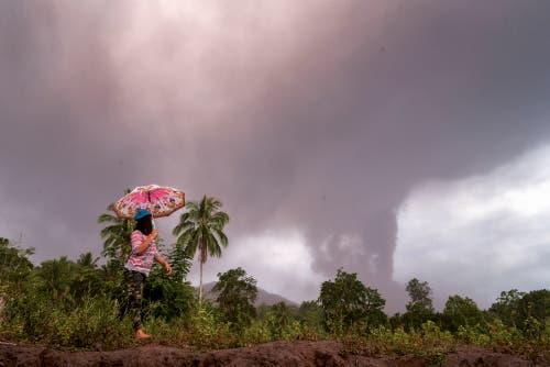 Eine Bewohnerin der Insel Sulawesi spaziert am aschespeienden Vulkan Soputan vorbei. (Bild: EPA/UNGKE PEPOTOH)