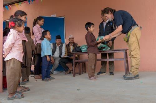 Die Schulhäuser wurden mit Hilfe aus dem Kanton Uri wieder aufgebaut. Der Altdorfer Heinz Gisler beschenkt die Kinder (Bild: PD)