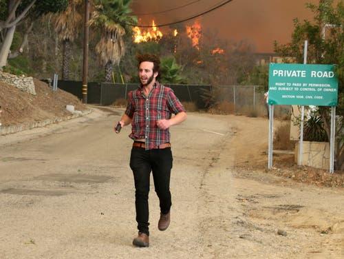 Anwohner versuchen ihre Häuser zu retten. (Bild: Reed Saxon/AP (Malibu, 9. November 2018))