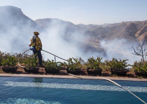 Ein Feuerwehrmann überwacht das Hinterland eines vom Feuer verschonten Hauses. (Bild: Eugene Garcia (West Hills, 11. November 2018))