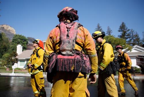 Ein kalifornischer Feuerwehrmann nach einem Brandbekämpfungseinsatz mit rot verfärbtem feuerhemmenden Mittel. (Bild: Eugene Garcia (West Hills, 11. November 2018))