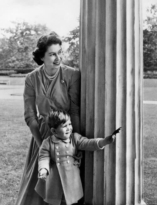 Königin Elizabeth II. schaut mit dem zweijährigen Prinz Charles hinter einer Säule hervor, aufgenommen am 20. Oktober 1950 auf dem Grundstück von Clarence House in London. (Bild: Archiv KEYSTONE/Str)