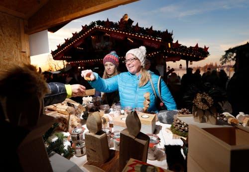 Weihnachtsmarkt Zug: Jenny (links) und Tanja Michlmayr kriegen am Stand der Zuwebe ein Guetzli zum probieren. (Bild: Stefan Kaiser, Zug, 8. Dezember 2016)
