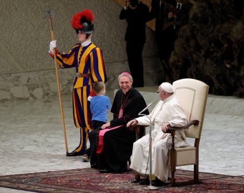 Der Junge wuselt auf der Bühne herum. Doch das nehmen die beiden Kirchenvertreter mit Humor. (Bild: Gregorio Borgia, Rom, 28. November 2018)