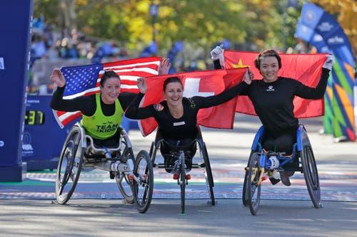 Neben Schär feiert Tatyana McFadden (links) aus den USA ihren zweiten und Lihong Zou (rechts) aus China ihren dritten Platz. (Bild: AP Photo/Seth Wenig, 4. November 2018))