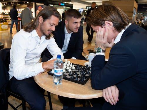 Adrian Winter (links) und Hekuran Kryeziu vertreiben sich die Zeit vor dem Abflug mit einer Partie Schach (Bild: KEYSTONE/MELANIE DUCHENE)