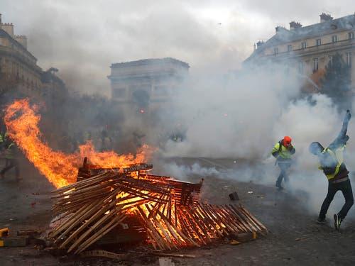 In der Nähe des Triumphbogens in Paris haben Demonstranten der «Gelbwesten»-Bewegung Absperrungen in Brand gesetzt. (Bild: KEYSTONE/AP/THIBAULT CAMUS)