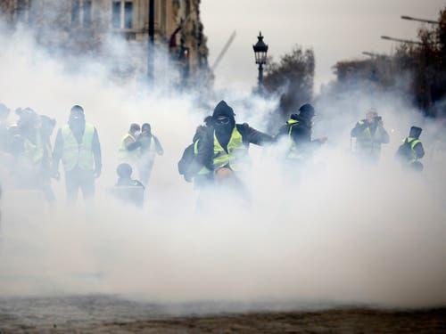 Aktivisten der «Gelbwesten»-Bewegung haben ihre Proteste gegen die Politik von Staatschef Emmanuel Macron in Paris fortgesetzt. Dabei kam es zu Ausschreitungen mit der Polizei, die auch Tränengas einsetzte. (Bild: KEYSTONE/AP/KAMIL ZIHNIOGLU)