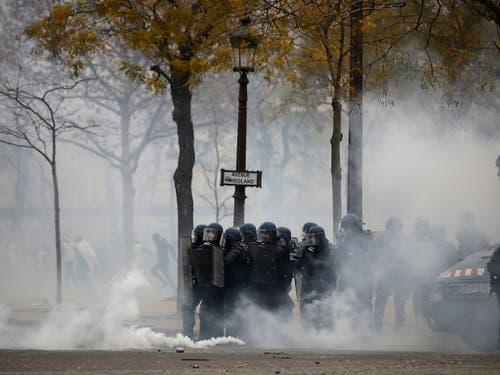 Tränengaseinsatz der Polizei auf den auf den Champs-Elysées in Paris als Aktivisten der «Gelbwesten»-Bewegung bei neuen Protesten eine Sperre durchbrechen wollten. (Bild: KEYSTONE/AP/KAMIL ZIHNIOGLU)