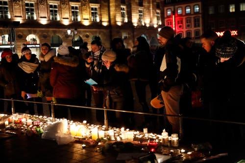 Viele Menschen sind zusammengekommen und haben Kerzen zum Gedenken aufgestellt. (Bild: AP/Christoph Ena)