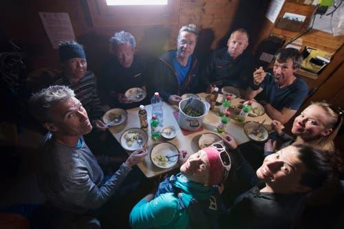 Die siebenköpfige Gruppe mit ihren beiden Bergführern in der Hütte. Das einfache Leben schweisst das Team zusammen. (Bild: PD/SRF)