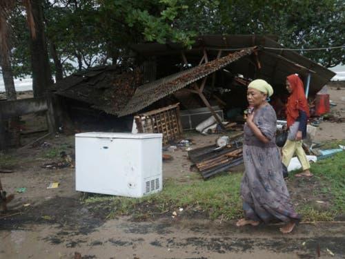 Bis zu 20 Meter hohe Wellen: Bewohner vor ihren vom Tsunami zerstörten Häusern in Carita in Indonesien. (Bild: KEYSTONE/AP/DIAN TRIYULI HANDOKO)