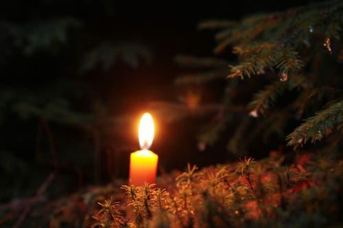 Am Weihnachtstag leuchtet eine Kerze auf dem Waldboden. (Bild: Irene Wanner (Schötz, 25. Dezember 2018))