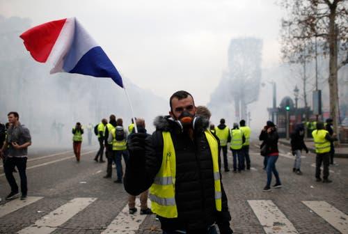 Ein Demonstrant schwingt die französische Tricolore auf der Avenue des Champs-Élysées. (Bild: Rafael Yaghobzadeh/AP Photo (Paris, 08.12.2018))